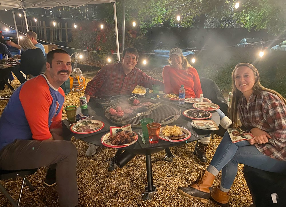 A family of four sitting around a gather grill tailgater while food is being grilled