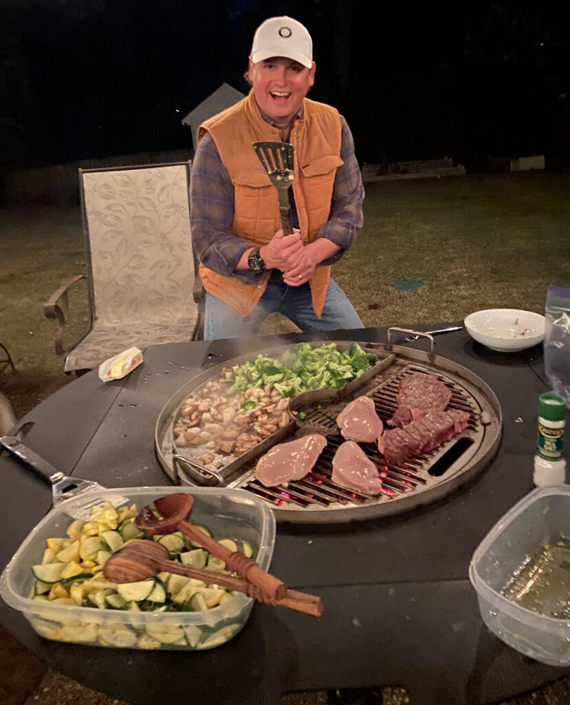 Smiling man holding a spatula cooking a variety of vegetables and steak on a gather grill combo