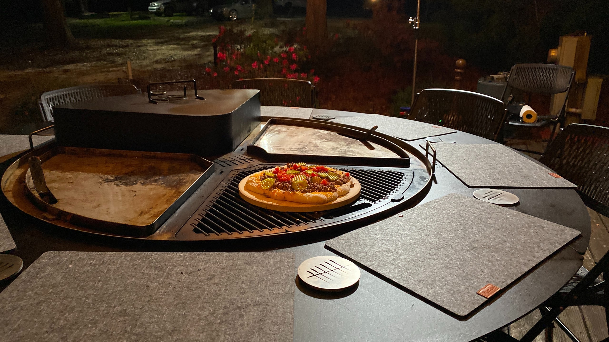 A cooked pizza served on an otherwise empty gather grill