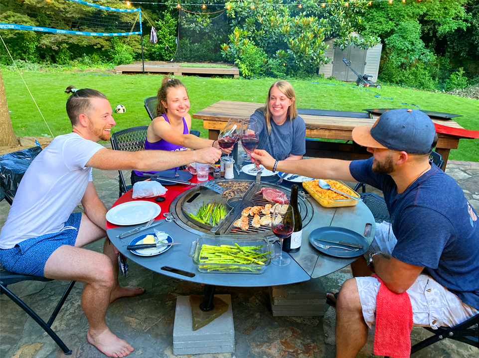 four people seated around a grill combo clinking their wine glasses together in a toast