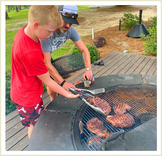 A man teaching a child to flip a steak using tongs