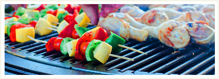 Vegetarian skewers and chicken legs pieces being grilled on a gather grill