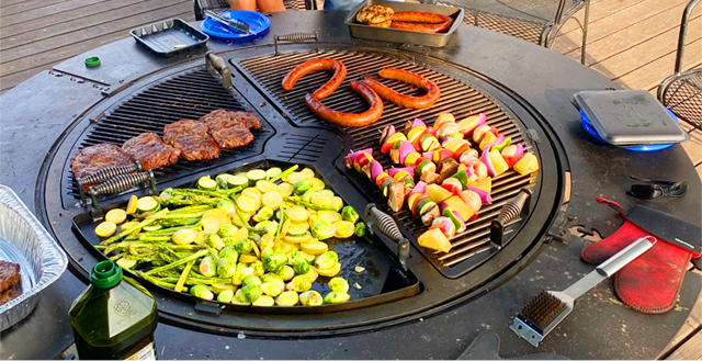 Sausages, skewers, steaks and a variety of vegetables cooking on a gather grill
