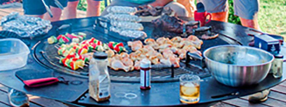 Skewers, chicken and a variety of other food being cooked on a gather grill