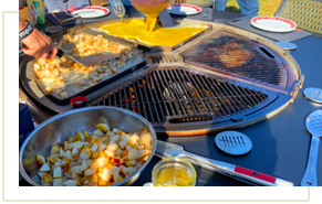 Mixed eggs being poured onto the griddle attachment of a gather grill while potatoes are being cooked to the side.