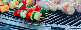 Vegetable skewers and chicken legs being cooked on a gather grill