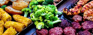 Broccoli, corn and meat being grilled on a gather grill