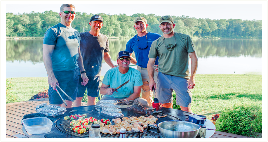Five men standing by a large circular Gather Grill which is loaded up with vegetarian and chicken skewers as well as barbeque. To the left there is a separate image of the gather grill unoccupied.