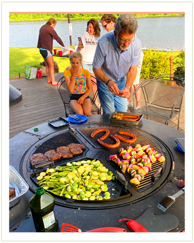 A man cooking sausages, skewers, steaks and a variety of vegetables on a gather grill