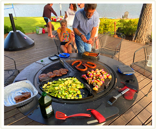 A man cooking sausages, skewers, steak and a variety of vegetables on a gather grill