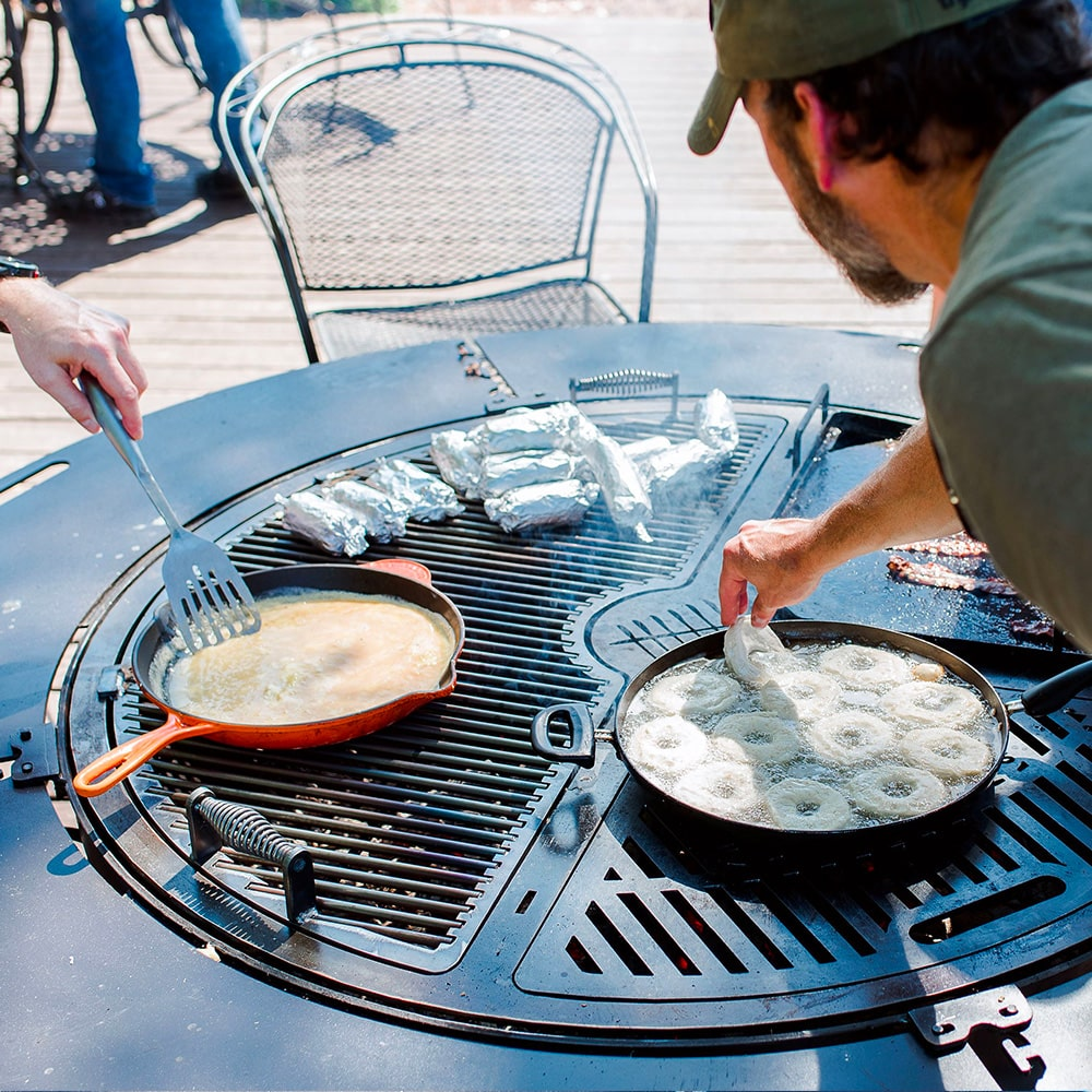 A gather grill combo loaded with a variety of food wrapped in foil, being tended to by two men.