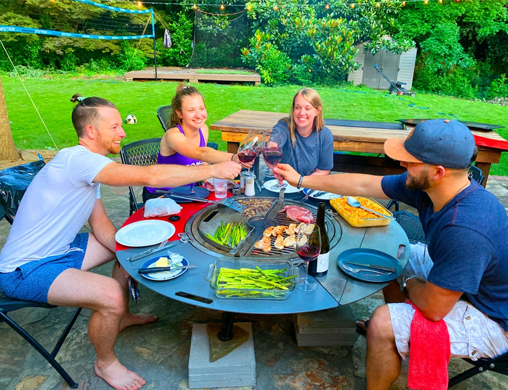 four people seated around a grill combo clinking their wine glasses together in a toast.
