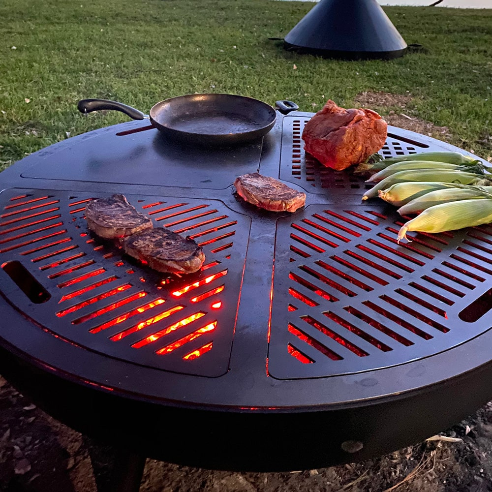 The grill combo is occupied on all its four sections with pork chops, unhusked corn and other meat as well as a sauté pan.