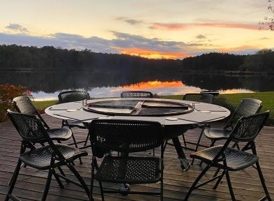 A gather grill combo surrounded by six chairs, on a patio by the lake, at sunset