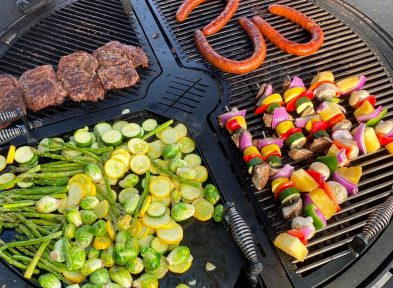 A variety of vegetables and hotdogs being cooked on a gather grill