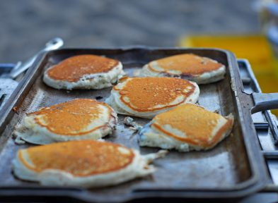 Several pancakes being cooked in a cast iron skillet on a grill